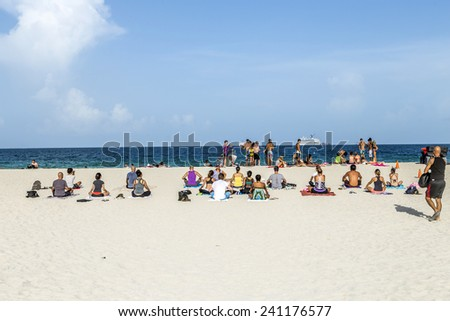 MIAMI, USA - AUGUST 18, 2014: People at the sea side meditate at the beach in Miami, USA. Miami Beach is a popular destination among tourists, spiking during the winter time.