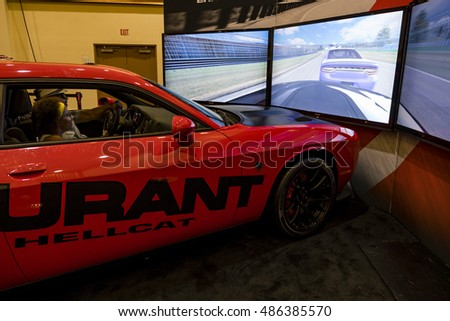 MIAMI, USA - SEPTEMBER 10, 2016: Visitors enjoy the Dodge racing simulator during the Miami International Auto Show at the Miami Beach Convention Center.