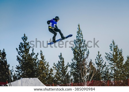 Miass, Russia - February 20, 2016: young athlete snowboarder rides through snow-covered mountain slope during Snowboard World Cup - Snowboard Cross - stock photo