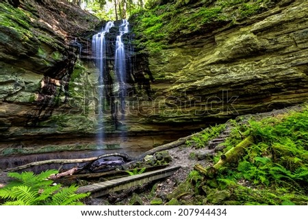 Michigan waterfall with a wooden footbridge across the ravine at the base.  Munising, Michigan   - stock photo