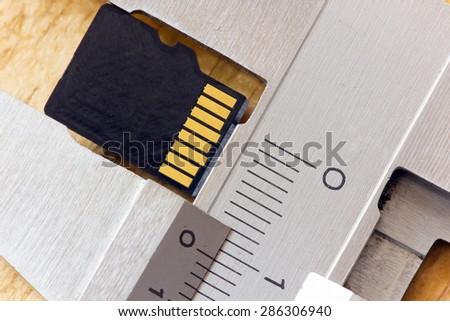 micro sd card is measured using caliper - stock photo