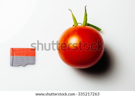 Micro SD card Secure Digital next to red cherry tomato
