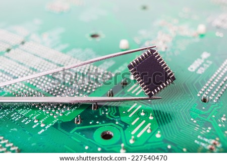 microchip in the tweezers closeup on the background of the motherboard - stock photo