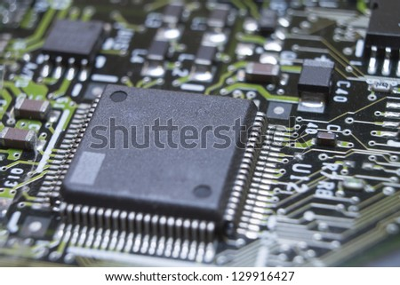Microchips surrounded by other elements on a circuit board