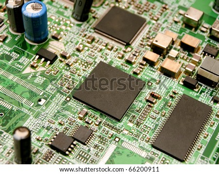 Microchips surrounded by other elements on a circuit board - stock photo