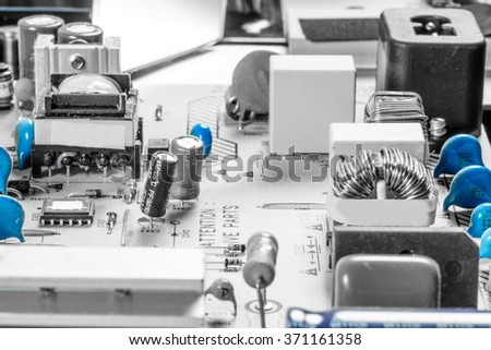 Microcircuit board with capacitors and chips in blue color - stock photo