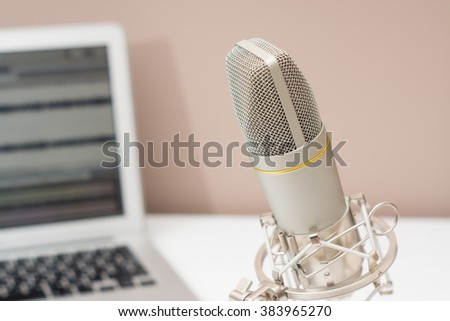 Microphone and a computer on a table in a studio. Sound recording theme image