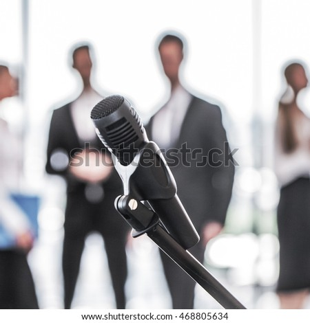 Microphone and business team on background, presentation concept