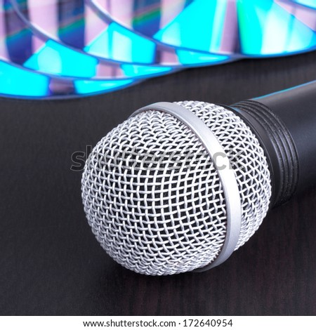 Microphone and compact disks on black table,closed-up - stock photo