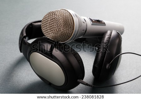 Microphone and ear-phones on a table - stock photo