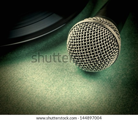 microphone and old vinyl record on a green background - stock photo