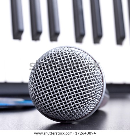 Microphone and piano keyboard on black table,closeup in studio
