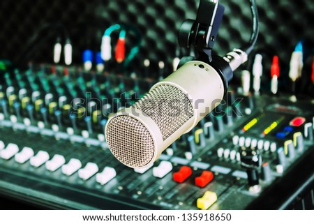 microphone and the mixing desk sound studio background - stock photo