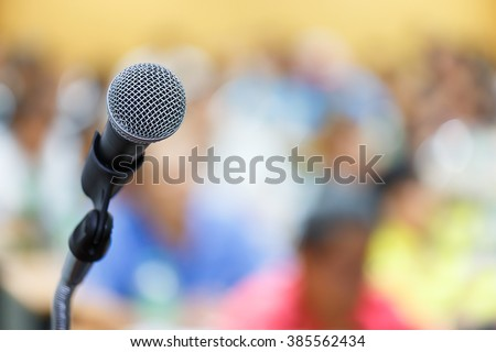 Microphone close up shot in seminar or meeting room with people in blur focus for copy space - stock photo