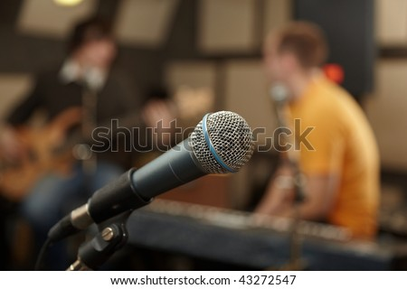 microphone. guitar player and keyboarder in out of focus - stock photo