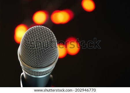Microphone head with stage lights in background. - stock photo