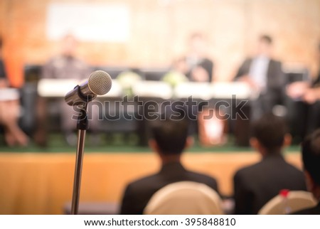 Microphone in business conference room with blurred speaker in background, Extremely shallow dof