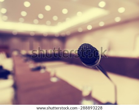 Microphone in concert hall or conference room with de focused bokeh lights in background. Extremely shallow dof. : Vintage style and filtered process - stock photo