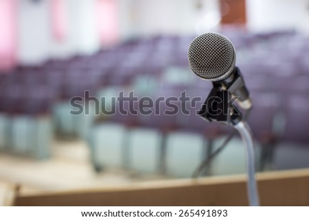 Microphone in concert hall or conference room with defocused bokeh lights in background