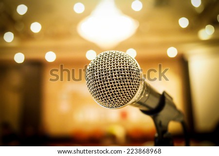 Microphone in concert hall or conference room with defocused bokeh lights  in background. Extremely shallow dof. - stock photo