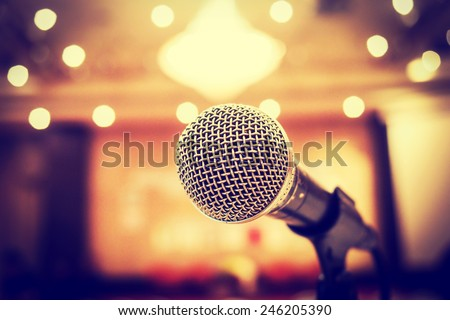 Microphone in concert hall or conference room with defocused bokeh lights  in background. Extremely shallow dof. : Vintage style - stock photo