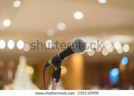 microphone in concert hall or conference room with lights in background. with extremely shallow dof.. - stock photo