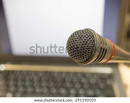 Microphone in  conference room or Symposium event with de focused laptop in background.