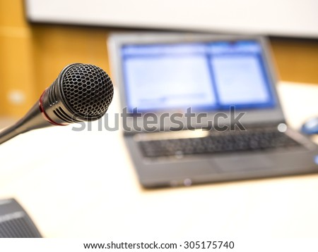 Microphone in conference room or symposium event with de focused laptop is working in background. - stock photo