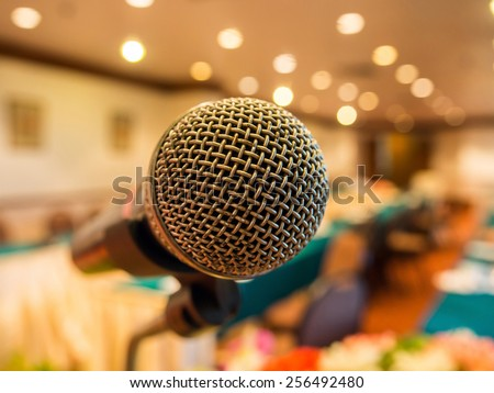 Microphone in  conference room with defocused bokeh lights in background. Extremely shallow dof. - stock photo