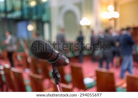 Microphone in focus against blurred chairs and standing talking audience