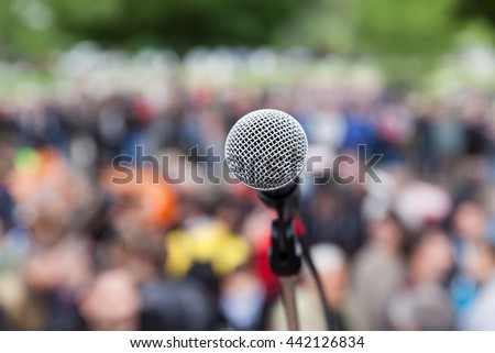 Microphone in focus against blurred crowd - stock photo