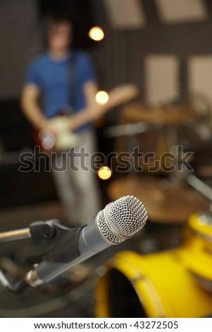 microphone in focus. guitar player in out of focus - stock photo