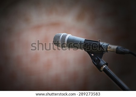 microphone in front of an old blurred brick wall with a light spot, narrow depth of field and copy space