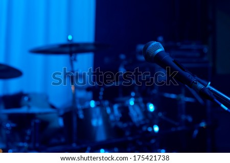 Microphone in front of the bands instruments standing ready on a stage for a live performace at a rock or jazz concert or festival in colourful blue lighting - stock photo