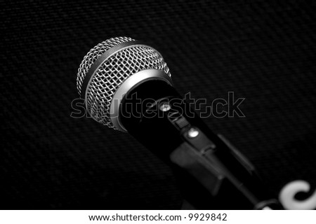 Microphone in front of the black textile on a guitar amp - stock photo