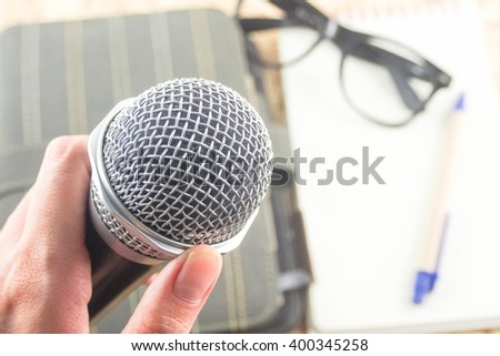 microphone in hand conference room blurred eyeglasses notepaper pen on table - stock photo