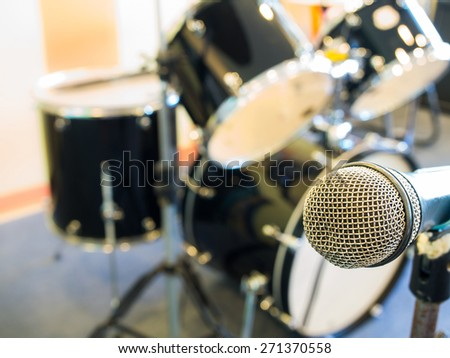 Microphone in  in a recording studio or concert hall with drum in out of focus background. - stock photo