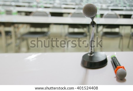 microphone in meeting room without people with light tone presents brightness from corner - stock photo