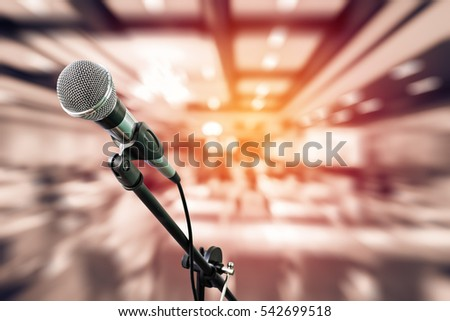 microphone in meeting seminar room or event hall with blurred people and seat background