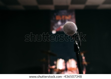 Microphone in music studio on black blurred background closeup. Front view on mic before performance against the background of blurred drum set.