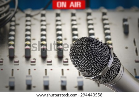 Microphone in sound studio with sound dashboard background.