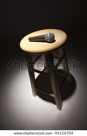 Microphone Laying on Wooden Stool Under Spotlight Abstract. - stock photo