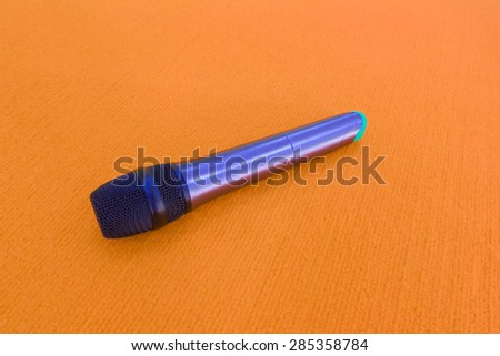 Microphone on a orange background. - stock photo