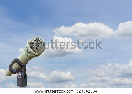 microphone on a stand over blurred cloudy blue sky - stock photo