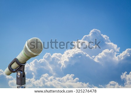 microphone on a stand over blurred cloudy blue sky. - stock photo