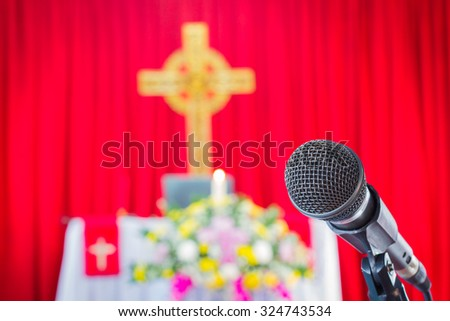 microphone on a stand with blurred cross in christian church  - stock photo