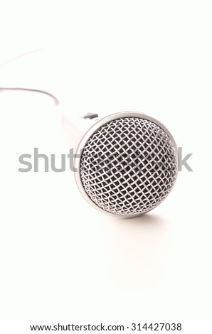 Microphone on a white background, selective focus on foreground with bright background - stock photo