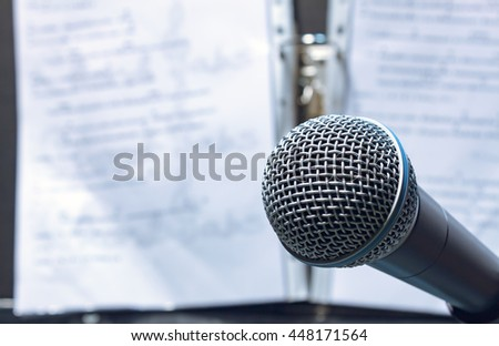 microphone on lyric sheets music background.