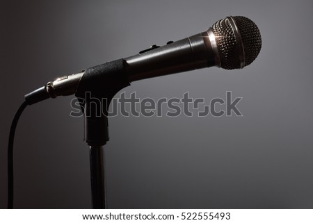 Microphone on microphone stand in the dark with gray background. Front view. Horizontal composition.