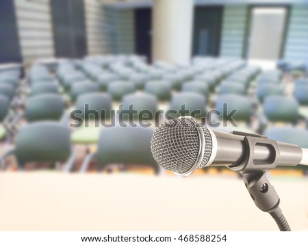 microphone on podium seminar study public speaking on blurred chair background